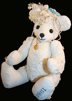"""This is a sweet 12"""" teddy bear made from my wedding dress, intended to be handed down to future grandchildren.  She is something new, made from something old, and features a blue satin flower made by my grandma (something blue) and is wearing the locket given to me as a baby by my grandparents, whose photos are inside the locket, which is 'something borrowed' from my childhood.  CUSTOM MEMORY BEARS FOR YOU by Lori Pappas, www.loribelledesigns.com"""