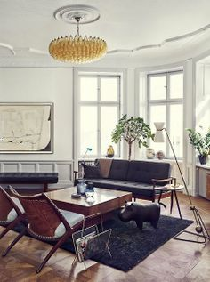 The apartment of Joanna Lavén in Stockholm, featude in Elle Decoration Sweden: A leather hippo by Dimitri Omersa  Co for Svenskt Tenn, Pierre Guariche floor light (ca.1950s), Carlo Scarpa chandelier for Venini and Krysset lounge chairs by Fredrik Kayser for Vatne Møbler, Norway. Photograph by Jonas Ingerstedt. / Dust jacket