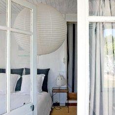 Une déco de chambre grise et blanc qui mise sur la simplicité et la combinaison des lignes : verticales pour le rideau de porte à rayures noires et grises, ronde avec la suspension en papier japonais et 2 carrés noirs apportés par les taies d'oreillers.