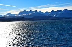 Snow covered arctic mountain tops across the water. Picture taken on a windy but sunny autumn day . See more pictures and videos of excotic Northern Norwegian arctic nature at: nordlandnature.com