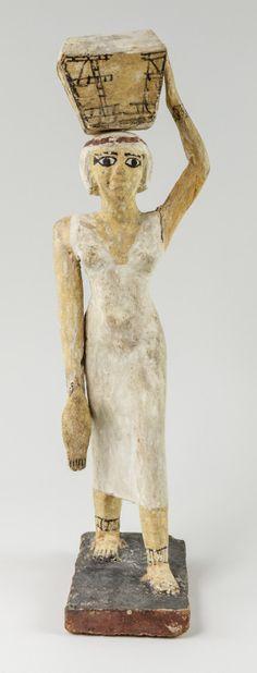 Statuette of a Female Offering BearerThis wooden statuette...