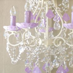 """This spectacular vintage-inspired 5-light chandelier has been painted a beautiful antique white and adorned with stunning Milky-Opal Lavender French pendants and matching fancy-cut glass bobeches. Plenty of crystal teardrops and layers of crystal chain swags add loads of glam and sparkle. What a creative way to bring a touch of lavender into a room: fresh, exciting, unique and all together decadent! <BR><BR> The chandelier measures 17"""" wide across the arms and 23"""" long down to the sparkly…"""