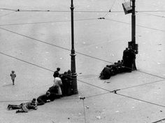 People seeking shelter behind lamp-posts at Dam square Amsterdam after German troops opened fire. 1945.