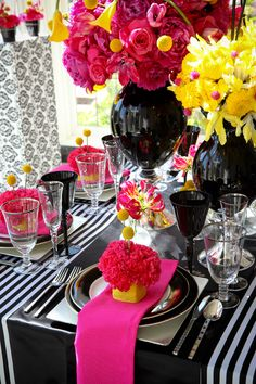 Black and white linen with black vases filled with hot pink and yellow flowers.