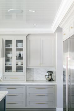 Gorgeous light grey cabinets, marbled countertops & backsplash, white trim & gold hardware. ❤