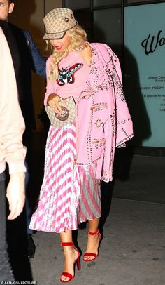 In the pink: Topping her VERY colourful look off, she slung a tacky studded pink leather jacket over her shoulders