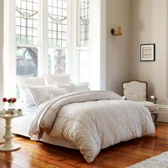 Love the stained glass bay windows above the bed, coupled with polished pine floorboards.