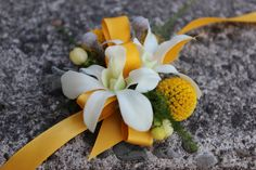 Yellow and gray wedding wrist corsage with orchids, hypericum, craspedia {billy balls}, dusty miller, silver brunia and plumosa