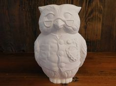 Whimsical collectible Wise Owl, unpainted, bisque fired, retro, figurine made from a vintage mold This owl is what I imagine as the coveted ceramic owl passed to the teacher of the month each month on that sitcom Mike and Molly.  He is distinguished, wearing reading glasses, dressed in his patched vest with pocket watch.  He stands about 7 1/2 Tall and about 5 wide.  Great in a gift basket, add some acrylic or enamel paint, some clear coat, and some paint brushes and youre good to go.  ...
