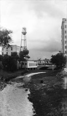 Ca. 1929 - This is what the San Antonio River looked like before the River Walk was built in the 1930's. San Antonio River between St. Mary's and Navarro Streets. Photo shows view looking upstream (east) toward the Navarro St. Bridge. On the left are buildings and water tower of Walthall Music Co. (southwest corner of Market and Navarro Streets). (UTSA Special Collections)