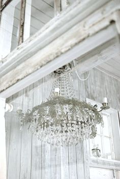 whitewashed room with amazing chandelier<3