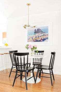 """A cozy but comfortable dining room is hard to pull off! Drawing the eye upward with the simple chandelier is a one-step trick and expanding the space with this <a href=""""http://bit.ly/1VK2wHo"""" target=""""_blank"""">Gray Malin</a> beach photo (and check out his <a href=""""https://www.graymalin.com/la-dolce-vita"""" target=""""_blank"""">new collection by the way</a>. It's amazing.) is transportive, no?"""
