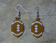 These cute little football earrings are done in the brick stitch with size 11 delica glass beads. They measure 1 long. The colors that I have used are tree bark brown and white. The designer is De Lynn Nelson. I do all of my own bead work one bead at a time. Thank you for looking at my bead work. Have a blessed day.