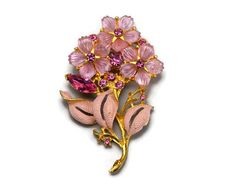 Vintage Pink Molded Lucite and Rhinestone Flower Bouquet Brooch or Pin, Pink Enamel Leaves, Gold Tone Metal Adorable vintage brooch with three pink daisy like flowers. The petals are molded lucite or plastic. Pink rhinestone centers. The leaves are painted pink enamel. Various other rhinestones dot the arrangement. Set in gold tone metal. It measures 2-7/8 inches tall and 1-3/4 inches wide. Unsigned. The pin is straight and the safety clasp is also secure. Slight wear to the enamel...
