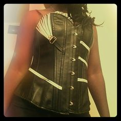 Faux leather boned corset This adorable steampunk styled corset  is a one shoulder. I have worn it strapless as well simply uncool the back strap. Pull the black strap through the metal clip and tuck the right side piece that has the white string. The size is an XL according to the measurements. 28 inches fully closed in and can open up to add 4 more inches. Tops