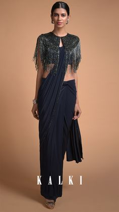 Let the delicacy of the navy-tinted hue brighten the sartorial sensibility of a fashion-faithful. Featuring the navy blue fringed cape saree style with a lavish makeover. The hand-crafted fringed capelet layered over a pre-draped saree makes it an ideal outfit for a day-to-night wedding functions