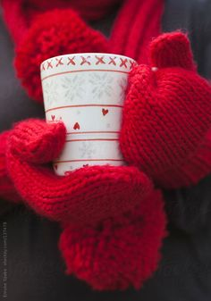 Person in red gloves holding a warm beverage in a white cup on a cold winter day