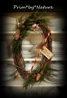 wreath combination of twigs, greens, rusty bells, pine cones and a large hand-wrapped raggedy candy cane