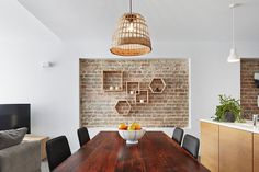 Lovely recessed brick wall in the dining room with geometric wooden shelves [Design: elaine richardson architect]