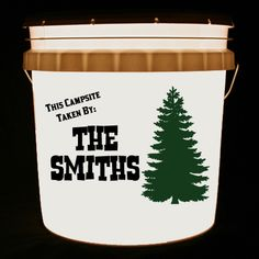 This bucket light is personalized with This Campsite Taken By and your family name, along with a dark green tree.