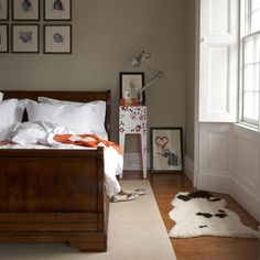 White bedding is particularly epicene, and the sleigh bed is simply traditional. But, the animal hide rug, Banksy artwork, and the floral side table give the impression that the space is shared by people with varying interests.