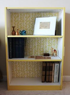 Bookshelf makeover.  Modge podge wrapping paper on the back of bookshelf to give it an updated look.