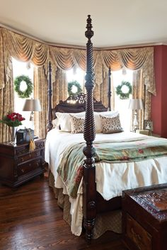 Wreaths at the windows, a vase of red roses, and gold tassels tied to a bedside chest serve as subtle Yuletide reminders.