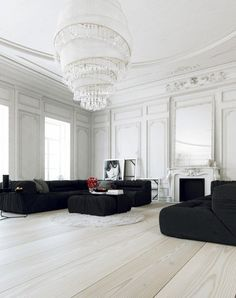 Stunning modern white crystal chandelier. Black couches pickled floors. Ornate moulding and stark white walls.