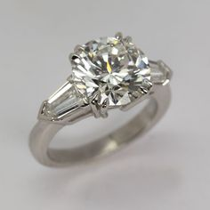 Round brilliant cut diamond engagment ring with baguette diamond side stones from Oliver Smith Jeweler.