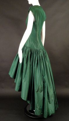 Stunning and VERY rare is this c.1970 couture evening gown in a dark forest green silk taffeta. My opinion is the gown was a special request from a 1950s model. It's the same gown only with a more mod