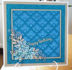 Using selection of Creative expression products. Teal and gold foundation card. Teal card embossed with Sue Wilson trailing leaf embossing folder. Teal 6 x 6 centre section masked with triple scallop msk using Phill Martins' graceful blue sparkly paste. Selection of Sue Wilson's Faux quilled blooms, petite vinery dies and finished with pierced flag tag.