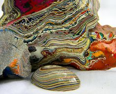 Fordite, also known as Detroit agate. It was formed from the build up of layers of enamel paint during automotive production. (I have a ring made from this. Very cool. No two are alike.)