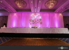 Gorgeous pipe and drape set up behind the head table at this pink uplighting wedding reception. Photo via #linandjirsa
