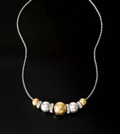 A study in symmetry and balance, this five-sphere necklace features one large, center sphere and four smaller spheres, two on each side. Accented with .35 ct. t.w. diamond discs. Sterling silver and 14kt yellow gold necklace.