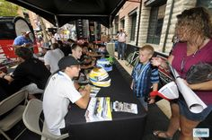 Gustavo Menezes signs autorgraphs for young fans at the Grand Prix of Baltimore Fan Village.