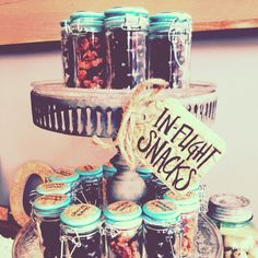 In-flight snacks for a travel themed bridal shower. Got the jars at World Market and filled them with chocolate covered almonds and pecan pralines from Trader Joes.