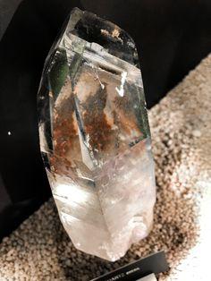 Un cristal de roche englobant des morceaux de pierre lui offrant de magnifique reflet rouille et vert.