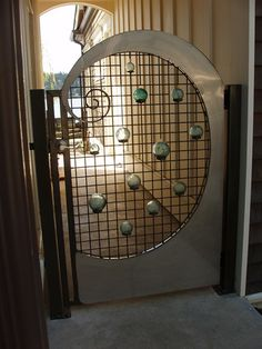 This is architectural design at its best, plus it's a functioning gate! A stainless steel custom gate with mossy green  glass spheres.
