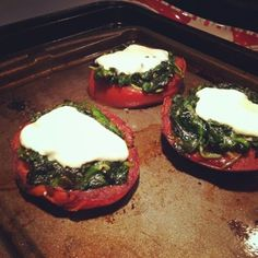 Marinate tomatoes in balsamic vinegar for 30 minutes. Lay on a baking sheet, season with salt and pepper. Bake for 7 minutes at 350 degrees. Then top with sauted spinach and mozzarella. Broil until cheese melts.