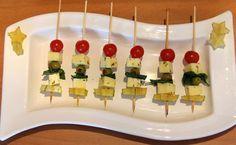 Tomate cereja, carambola (pode substituir por damasco ou abacaxi), queijo mussarela em cubos, folhas de manjericão, azeitona (preta sem caroço ou recheada com pimentão), azeite e orégano