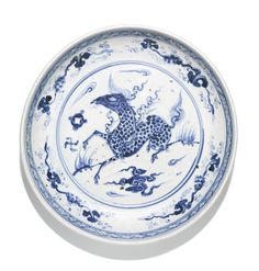 A BLUE AND WHITE 'QILIN' DISH MING DYNASTY, 16TH CENTURY the rounded sides supported on a tapered foot, freely painted to the interior with a central medallion enclosing a galloping qilin, encircled by four detached grape vines below a trellis band, the exterior similarly decorated with a lotus scroll 35.8 cm, 14 1/8 in. | sotheby's
