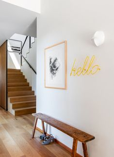 """A """"Hello"""" sign from UK-based Block Design, made from a single piece of powder-coated steel, hangs over a bench. #dwell #seattle #indooroutdoor #moderndesign #modernarchitecture Neon Signs Home, Neon Bedroom, Entry Stairs, Modern Hallway, Stair Decor, Indoor Outdoor Living, Staircase Design, Metal Furniture, Decoration"""