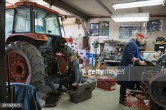 Stock Photo : Mechanics working on tractor in workshop
