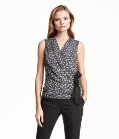 Sleeveless blouse in airy chiffon crêpe. Pleats at shoulders and attached, wrap-style front section with attached tie at side. Lined at front.