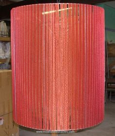 Custom large drum lampshade made of red ribbon.