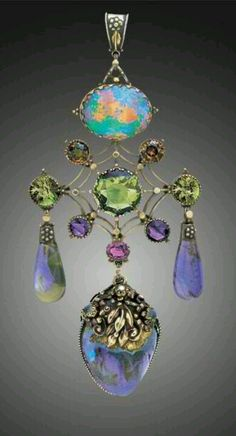 ARTIFICERS' GUILD 1901-1942  Superb Arts & Crafts Pendant Gold, silver, opal, sapphire, zircon, tourmaline, amethyst, almandine garnet, moonstone & pearl, Pendant length: 9.8cm Width: 4.3cm.English. Circa 1910 Original fitted case the silk marked: 'The Artificers' Guild Ltd 4 Conduit Street. London. W.' Literature: cf. Jewelry & Metalwork in the Arts & Crafts Tradition, Elyse Zorn Karlin, 1993, page 115