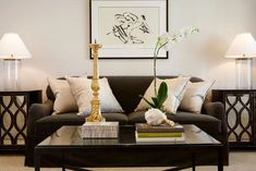 Ashley Goforth Design Beautiful living room with dark brown sofa filled with white and gray pillows flanked by mirrored end tables, Oly Studio Elisabeth Bedside Tables, with clear glass column table lamps and espresso coffee table with mirrored top. Dark Brown Couch, Brown Leather Sofa Living Room, Brown And Blue Living Room, Living Room White, Beautiful Living Rooms, Living Room Paint, New Living Room, Living Room Sofa, Apartment Living