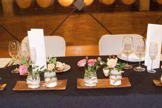 Centres de taula vintage amb arpillera i roses de pitiminí de color rosa.