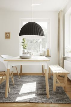 Kitchen table in wood with white details, white chairs and a giant lamp via 79 Ideas