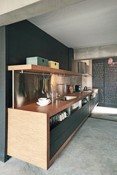 Cozinha decorada com madeira e preto com piso de cimento queimado
